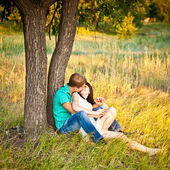 Young couple kissing under a tree — Stock Photo