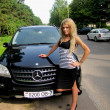 Blonde with a black Mercedes ML — Stock Photo