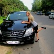 Blonde with a black Mercedes ML - Stock Photo