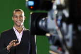 Presenter in TV Studio with foreground camera — Stock Photo