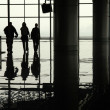 Silhouetted travellers in an airport terminal — Stock Photo