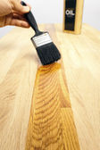 Brushing oil onto a wood surface — Stock Photo