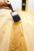 Borstelen van olie op een houten oppervlak — Stockfoto