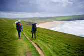 Backpackers walking Cornish Coastline — Stock Photo