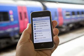 Using a UK Train Timetable App — Stock Photo