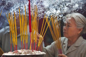 Woman with lit incense sticks — Stock Photo