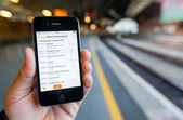 Using a Smartphone to Check Train Times and Platforms — Stock Photo