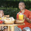 African American Family Healthy Eating Outside - Stock Photo