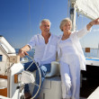 A happy senior couple sitting at the wheel of a sail boat - Stock Photo