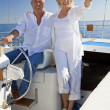 A happy senior couple sitting at the wheel of a sail boat — Stock Photo