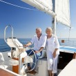 A happy senior couple sitting at the wheel of a sail boat — Stock Photo #21588599