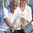 A happy senior couple sitting at the wheel of a sail boat — Stock Photo #21588623