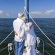 A happy senior couple embracing at the front or bow of a sail boat — Zdjęcie stockowe