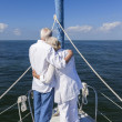 A happy senior couple embracing at the front or bow of a sail boat — Стоковая фотография