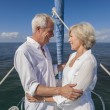 A happy senior couple embracing at the front or bow of a sail boat — Stock Photo #21588691