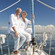 A happy senior couple embracing at the front or bow of a sail boat  — Stock Photo