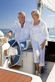 A happy senior couple sitting at the wheel of a sail boat — Photo