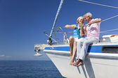 A happy senior couple sitting on the front of a sail boat — Stock Photo