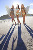 Three Beautiful Women Surfers In Bikinis With Surfboards At Beac — Stock Photo