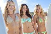 Three Beautiful Women Surfers In Bikinis With Surfboards At Beac — Stock Photo