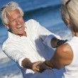 Happy Senior Couple Playing Holding Hands on A Tropical Beach — Stock Photo #21598429