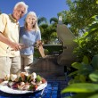 Stock Photo: Happy Senior Couple Outside Cooking on A Summer Barbecue