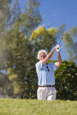 Happy Senior Man Playing Golf Ball Out of a Bunker — Stock Photo