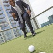 African American Businessman Playing Golf on Skyscraper Rooftop — Stock Photo