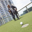 African American Businessman Playing Golf on Skyscraper Rooftop — Stock Photo #21600145