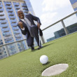 African American Businessman Playing Golf on Skyscraper Rooftop — Stock Photo #21600149