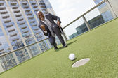 African American Businessman Playing Golf on Skyscraper Rooftop — Stok fotoğraf