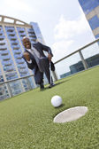 African American Businessman Playing Golf on Skyscraper Rooftop — Photo