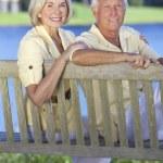 Senior Couple Sitting On Park Bench By Lake — Stock Photo #21638105