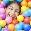 african american girl child colorful plastic balls — Stock Photo