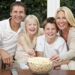 Happy Family Eating Popcorn Watching Television - ストック写真