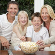 Happy Family Eating Popcorn Watching Television - Stock Photo