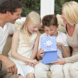Stock Photo: Happy Family Boy Child Opening Birthday Present At Home