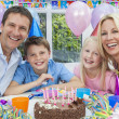 Family Celebrating Children's Birthday Party With Cake - Stock Photo
