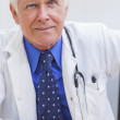 Senior Male Doctor With Stethoscope at Desk & Computer — Foto de Stock