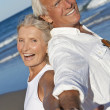 Happy Senior Couple Back to Back Holding Hands on Beach — Stock Photo