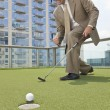 Successful Businessman Playing Golf on Skyscraper Rooftop - Stock Photo