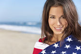 Young Woman Wrapped in American Flag Towel on a Beach — Stock Photo
