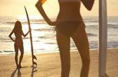Genç kadın bir plajda havlu amerikan bayrağı sarılı — Stok fotoğraf