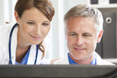 Male Female Hospital Doctors Using Computer — Stock Photo
