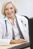 Senior Female Doctor With Stethoscope at Desk & Computer — Stock Photo