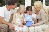 Lycklig familj pojke barn öppna födelsedagspresent hemma — Stockfoto