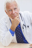 Senior Male Doctor With Stethoscope at Desk — Stock Photo