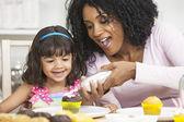 Afro-amerikaanse moeder gemengd ras dochter berijpen slagroom gebak — Stockfoto