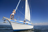 Beautiful Young Blond Woman on the Bow of a Sail Boat — Stock Photo