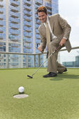 Successful Businessman Playing Golf on Skyscraper Rooftop — Stock Photo